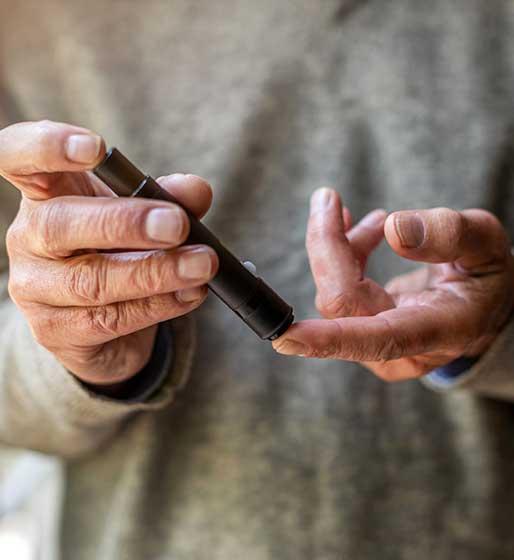 Hände eines älteren Menschen, die sich mit einem entsprechenden Werkzeug Blut für einen Glukose-Test entnehmen