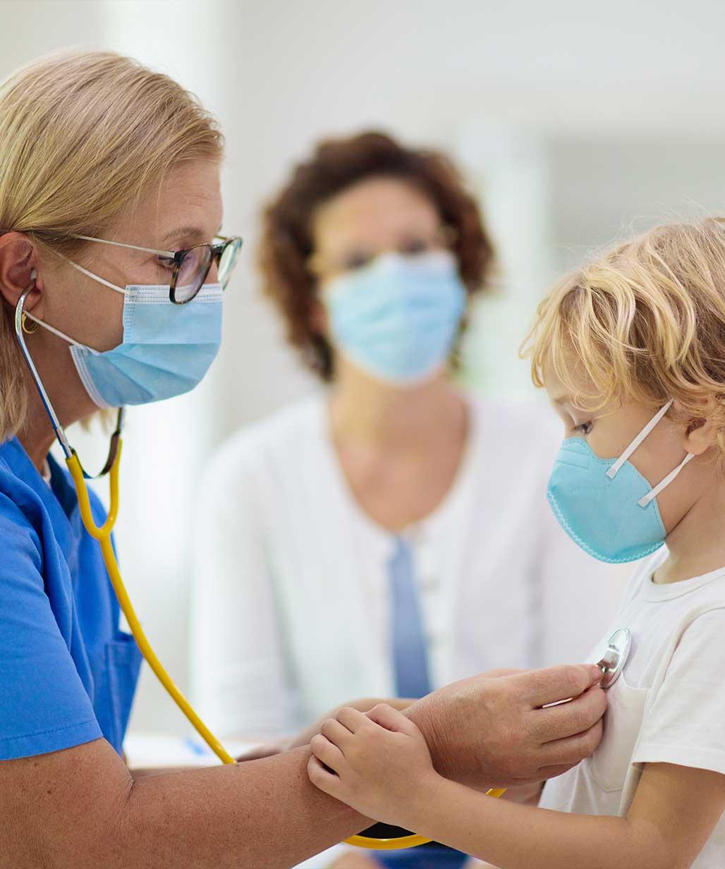 Kind wird von Ärztin untersucht, beide tragen eine medizinische Maske