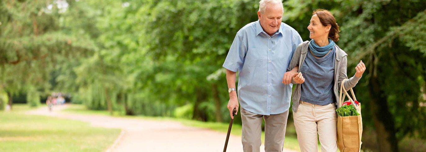 Alter Mann am Stock wird von Frau mittleren Alters gestützt, beide laufen lächelnd durch einen Park