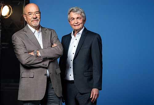 Zwei Herren mittleren Alters im Anzug, die in die Kamera lächeln