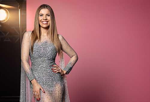 Die Moderatorin Victoria Swarovski, eine junge hübsche Frau mit langen blonden Haaren und glitzerndem Kleid, steht lächelnd vor einer rosa Wand