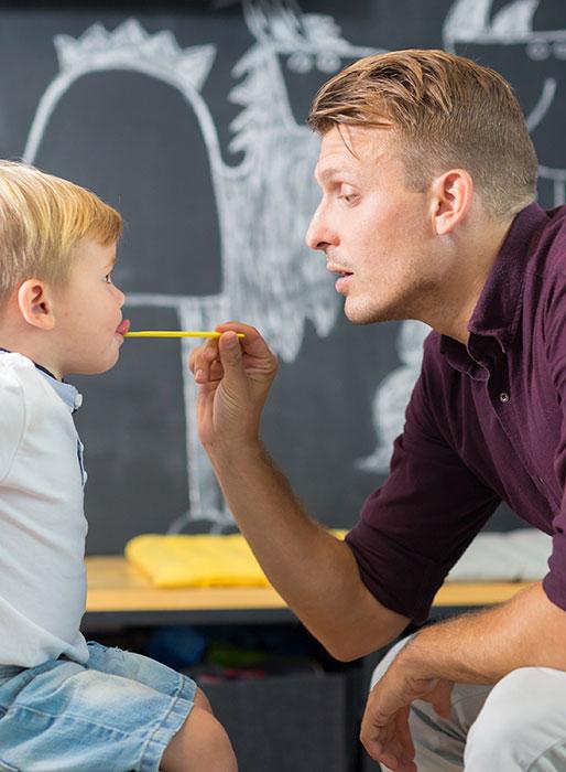 Bild zeigt Mann und Kind in logopädischer Behandlung