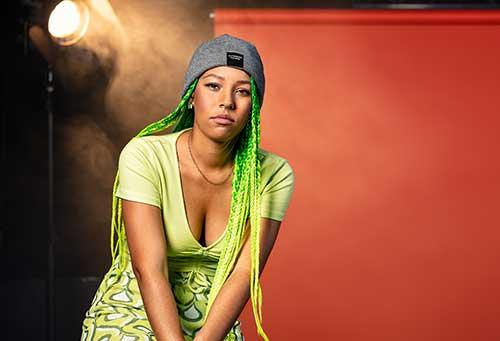 Junge Frau mit grünen Rasta-Zöpfen, Mütze und grünem Kleid, die ernst in die Kamera schaut