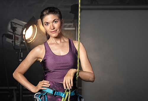 Junge Frau in Sportklamotten, die einen Klettergurt trägt